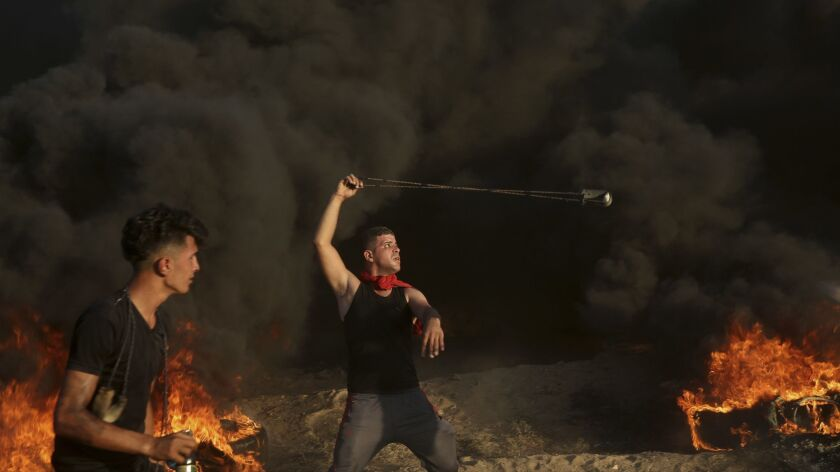 A protester hurls stones while others burn tires near the fence of the Gaza Strip border with Israel