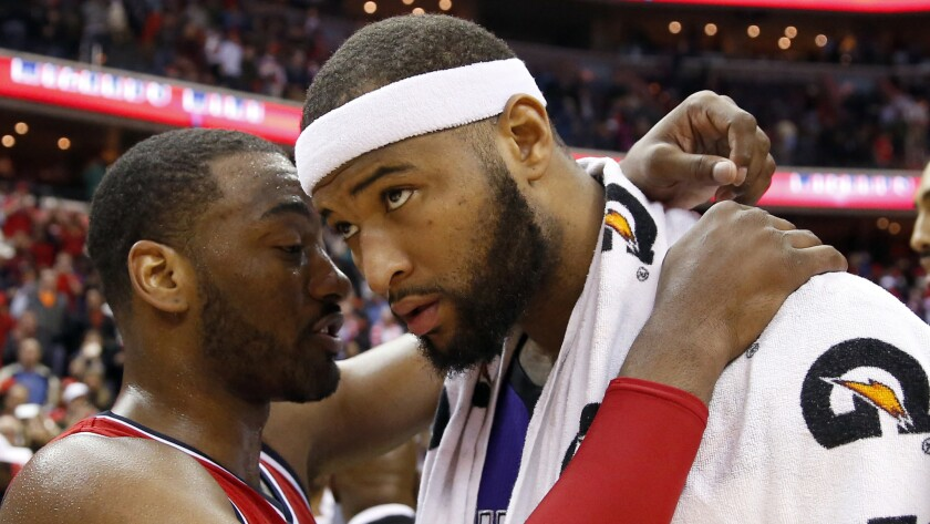 Washington Wizards guard John Wall, left, speaks to Sacramento Kings center DeMarcus Cousins after a game on March 14.