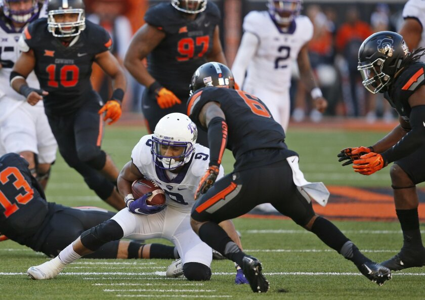 Oklahoma State cornerback Ashton Lampkin (6) moves in with other defenders to tackle TCU wide receiver Josh Doctson (9) in the second quarter of an NCAA college football game in Stillwater, Okla., Saturday, Nov. 7, 2015. Doctson was injured on the play and left the game. (AP Photo/Sue Ogrocki)