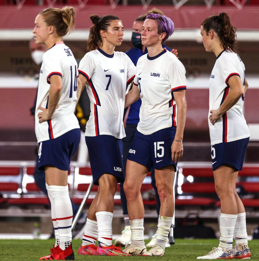 Soccer players Emily Sonnett, Tobin Heath, Megan Rapinoe and Kelley O'Hara stand on the sidelines at the Tokyo Olympics.