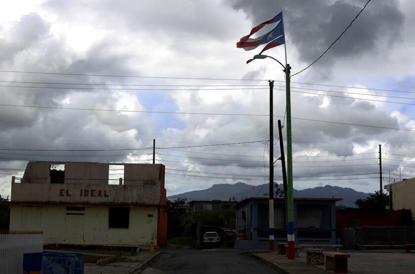 Fotografía del 18 de septiembre 2018, donde se muestra una bandera rota de Puerto Rico ondeando junto a una tienda destrozada por el paso del huracán María. EFE/Archivo