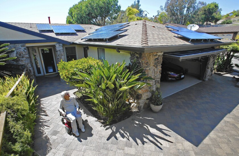 Cassina Tarsia cruises around her Oceanside home, which has enough solar panels on the roof to charge her wheelchair, her electric car, appliances and lights and even a storage battery.