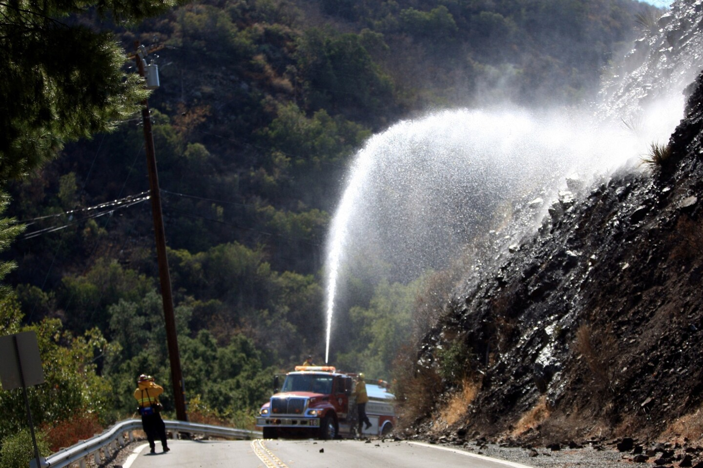 Orange County Fire Authority firefighters extinguish hot spots near homes on Silverado Canyon Road as crews battle the Silverado Fire in the Cleveland National Forest on Saturday.