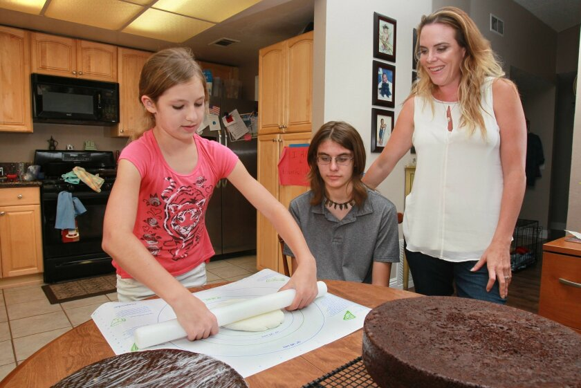 Tyler Lundhagen, 14, middle, watches his sister Brenna Lundhagen, 12, left, work on a wedding cake for an upcoming wedding of Autistic adults. Tyler and Brenna are also Autistic. At far right is Jenny Palmiotto, founder and organizer of the Love & Autism conference.