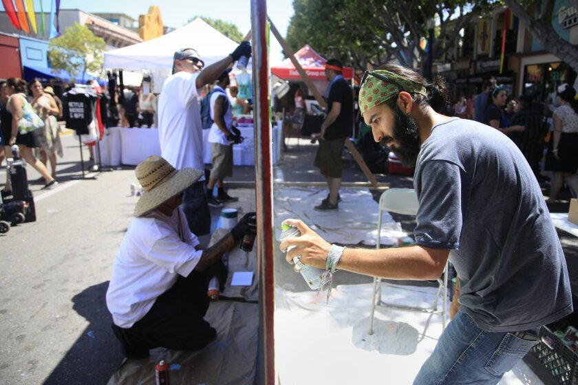 """Artist Nestor """"Spel"""" Mondragon, right, from Tijuana spray painted his artwork live during the 31st Annual Cityfest in Hillcrest Sunday afternoon."""