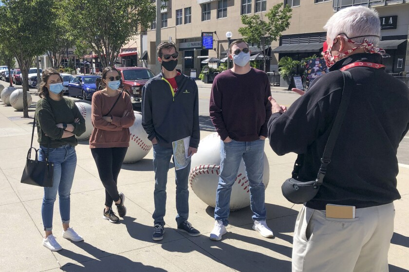 In this Sept. 20, 2020, photo, tour guide John Erardi, right, talks with a tour group on the sidewalk outside the Cincinnati Reds Great American Ball Park in Cincinnati. The walking tour was one of the few groups of people on the street as the Reds and White Sox were inside just an hour before the game without fans because of the pandemic. (AP Photo/Dan Sewell)