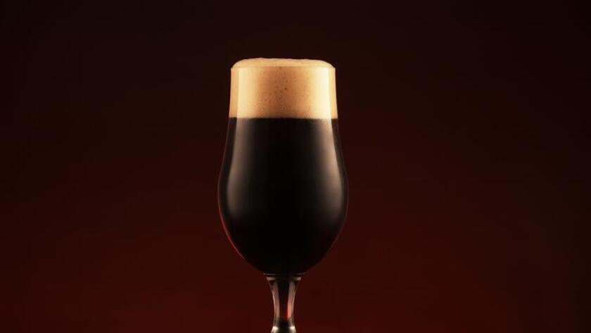 Dark beer in glass on wooden table.
