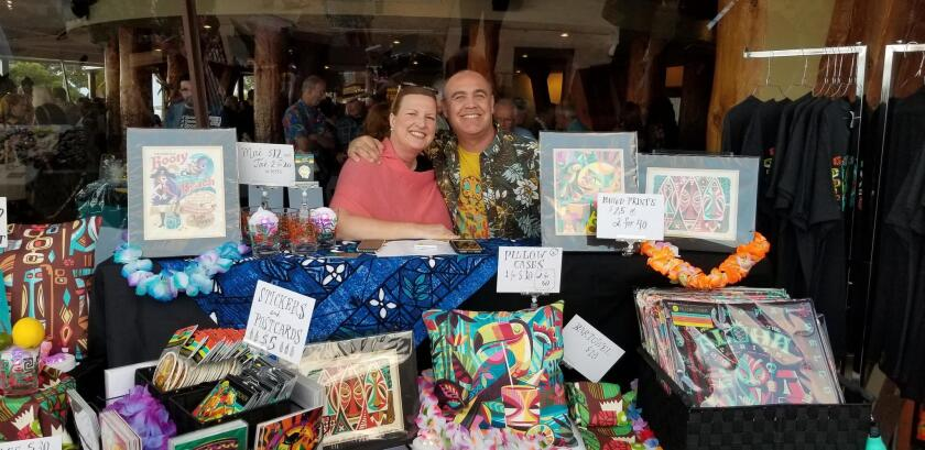 Jeff Granito of Jeff Granito Designs poses with his wife, Katy, at the stand displaying his art on pillow cases, stickers and postcards.