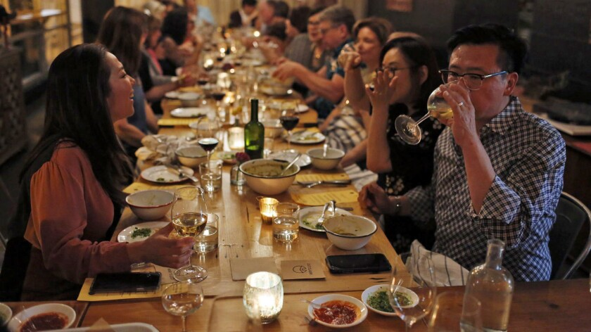 People enjoy a meal prepared partly by a refugee from Afghanistan during a New Arrivals Supper Club dinner in downtown Los Angeles.