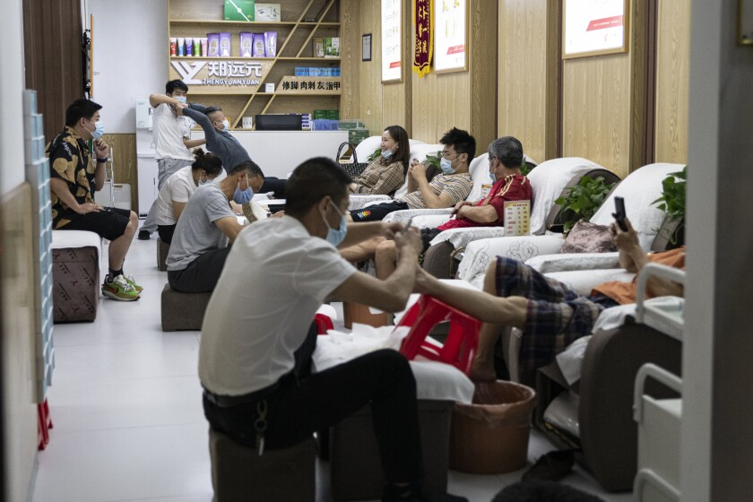 People in Wuhan wear protective masks in a massage parlor. Such businesses had finally begun to reopen.