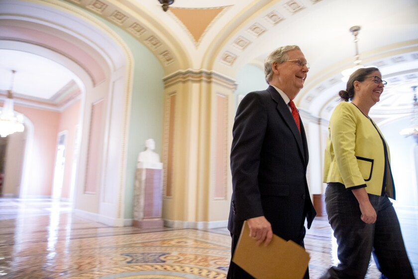 Senate Majority Leader Mitch McConnell, left, accompanied by Secretary for the Majority of the Senate Laura Dove, heads into the Senate chamber for a Sunday session on Capitol Hill in Washington, July 26, 2015.
