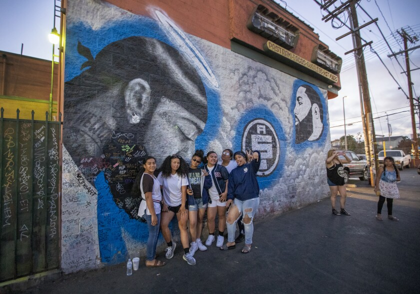 Tourists pose in front of a mural of slain rap star Nipsey Hussle.