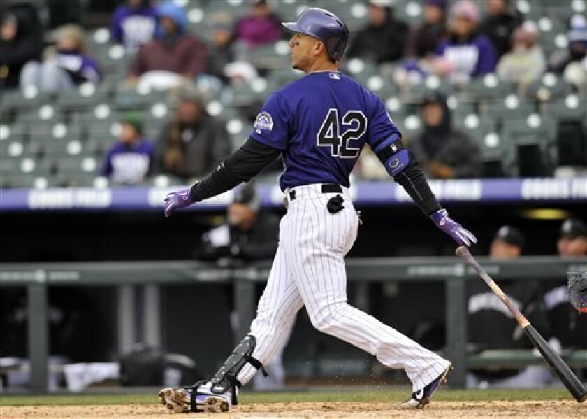 Colorado Rockies' Carlos Gonzalez watches the flight of a solo home run ball hit off New York Mets pitcher Dillon Gee during the third inning in the first baseball game of a doubleheader on Tuesday, April 16, 2013, in Denver. Players on both teams are wearing No. 42 in honor of Jackie Robinson. (AP Photo/Jack Dempsey)