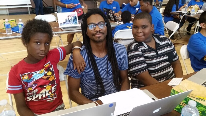 "DeCarlis Wilson, center, helps children learn to code at a ""hackathon"" organized by Teens Exploring Technology at the Nickerson Gardens housing project in Watts."