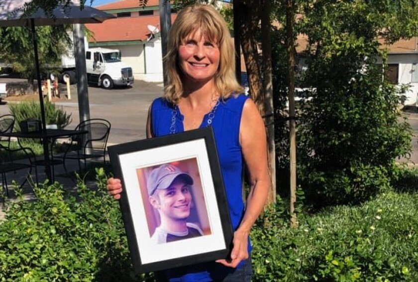 "Ramona resident Lorraine Kerz holds a photo of her late son Silas ""Sy"" River Bennett"