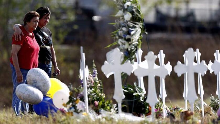 Maria Durand, izquierda, y su hija, Lupita Alcoce visitan las 26 cruces que representan a las víctimas de la masacre en la Primera Iglesia Bautista de Sutherland Springs, Texas. (Larry W. Smith / EPA / Shutterstock)