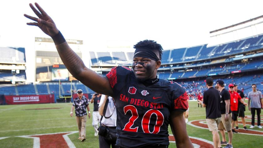 Aztecs' Rashaad Penny waves to fans after his final home game. Penny led the nation in rushing yards.