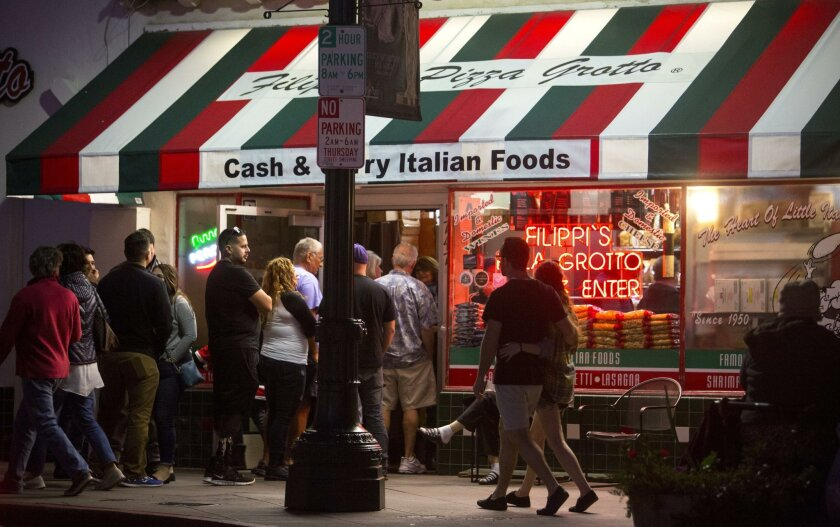 A line of patrons is out the door as people wait to get into Filippi's Pizza Grotto on India Street in Little Italy. Filippi's has been at the site since 1950, but a proliferation of new restaurants and rapid growth are reshaping the neighborhood.