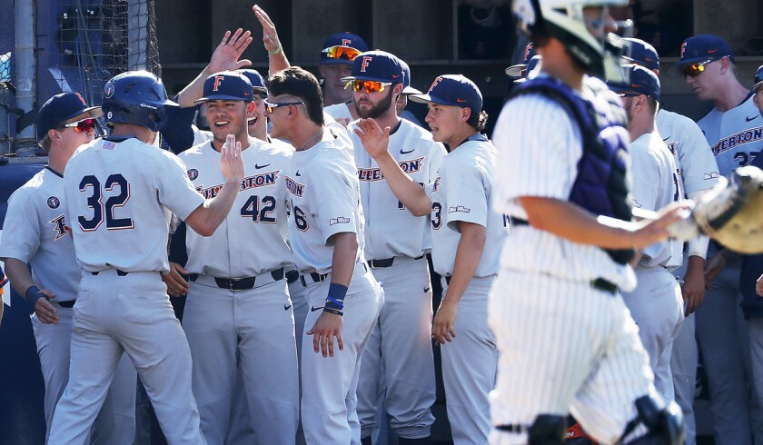 Cal State Fullerton's Jairus Rucahrds (32) is congratulated by teammates after scoring a run against