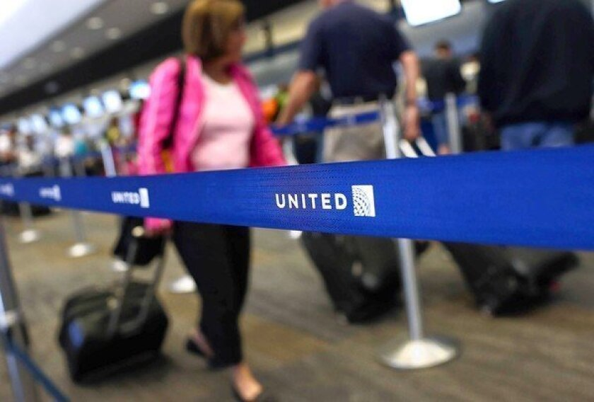United Airlines is planning to add slimmer seats to some of its planes to increase capacity. Above, United passengers wait in line at San Francisco International Airport.