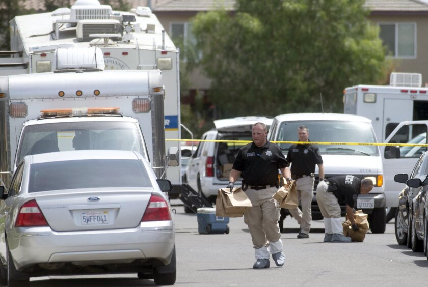 Police officers carry evidence bags at a crime scene where five bodies were found in a home July 18 in Modesto.