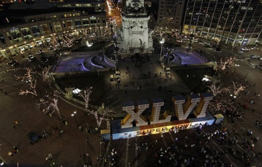 Fans have their photos taken in front of NFL football's Super Bowl XLVI sign on Monument Circle, Wednesday, Feb. 1, 2012, in Indianapolis. The Super Bowl is scheduled for Sunday, Feb. 5, between the New York Giants and the New England Patriots. (AP Photo/Darron Cummings)