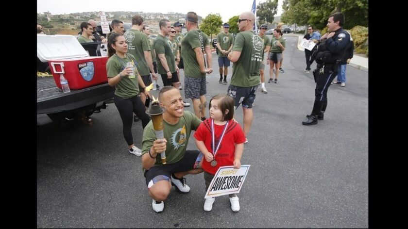 Laguna Beach Police officer Jeremiah Kennedy kneels with Rocco Keller, 5, during the annual Law Enfo