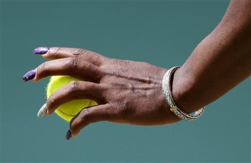 Serena Williams of the US prepares to serve during the match against Romania's Simona Halep at the All England Lawn Tennis Championships at Wimbledon, Thursday, June 23, 2011. (AP Photo/Alastair Grant)