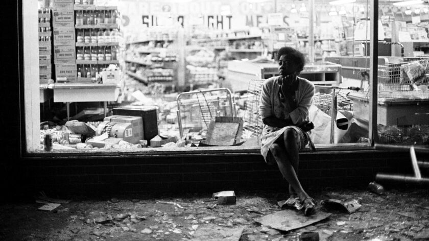 A woman sits outside a looted grocery store on Grand Boulevard on July 23, 1967.