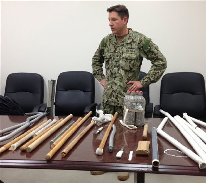 In this image reviewed by the U.S. Military, Navy Capt. Robert Durand stands next to some of the makeshift weapons, including broomsticks and batons made of plastic and steel, that were confiscated from prisoners at the Guantanamo Bay prison following a Saturday clash between prisoners and guards, on display for the press at the U.S. Naval Base Guantanamo Bay in Cuba, Tuesday, April 16, 2013. Soldiers with riot helmets and shields swept into recreation yards and met with resistance from several