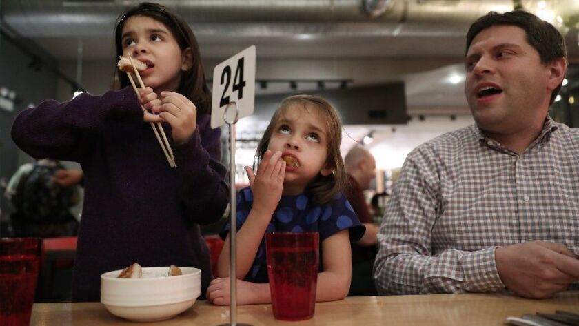 Sisters Emmy, 6, and Lila Nazemgoff, 4, eat chicken katsu as their father, Dan Goff, watches during dinner Jan. 9, 2019, at Urban Belly in Chicago's Wicker Park neighborhood.