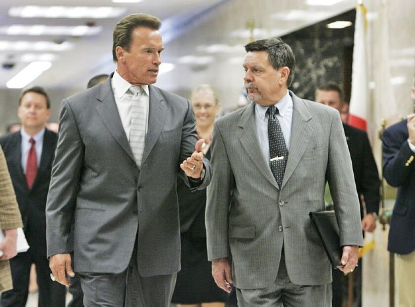 Gov. Arnold Schwarzenegger walked yesterday with Finance Director Mike Genest to a news conference to release the governor's proposed budget revisions.   (Rich Pedroncelli / Associated Press)