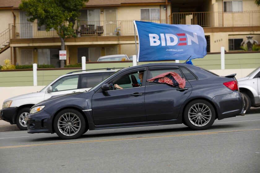 A Biden flag flies from a car during a car caravan in support of the Democratic presidential candidate