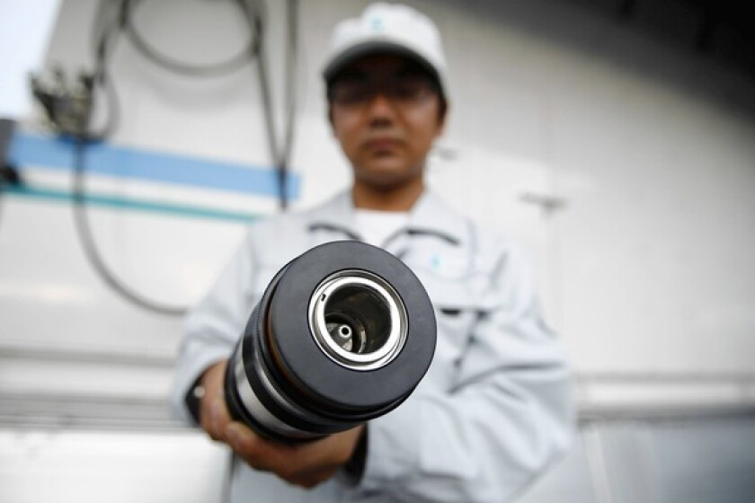 An employee at the Hydro Shuttle hydrogen station holds a refueling hose during a demonstration last month at a Toyota media briefing in Tokyo.