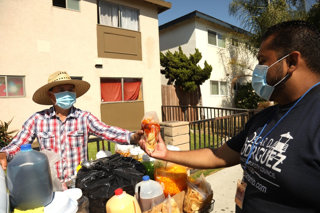 Longtime community activist Oscar Rodriguez, right, buys a bag of chips from street vendor Fernando Aguilar in Oak View.