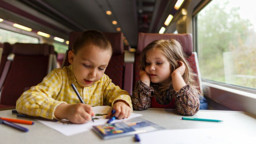 Young siblings drawing in the train