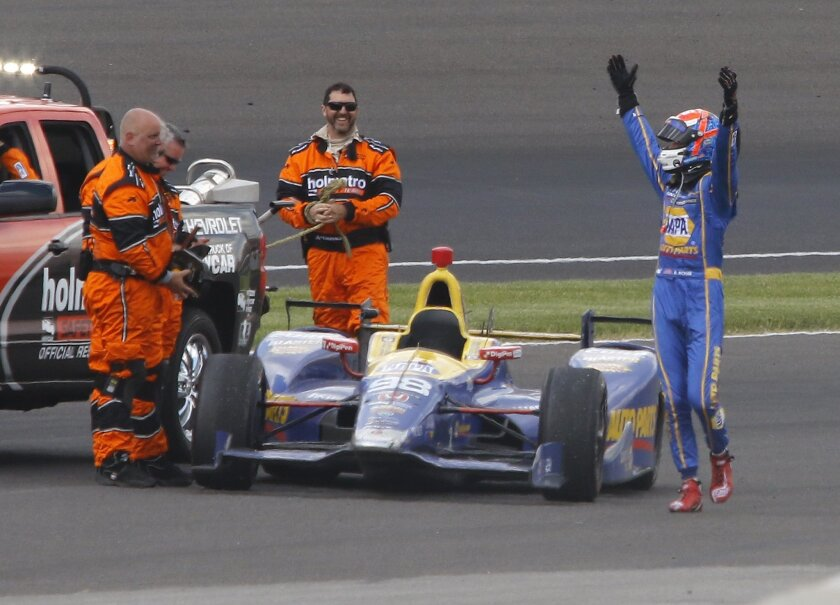 Alexander Rossi celebrates as he came to a stop in the fourth turn after running out of fuel after winning the 100th running of the Indianapolis 500 auto race at Indianapolis Motor Speedway in Indianapolis, Sunday, May 29, 2016. (AP Photo/Kirk Stierwalt)