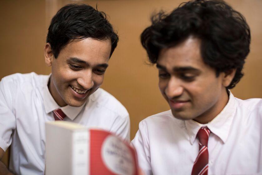 Schoolboys Brandon Ingram and Rehan Mudannayake look at a book