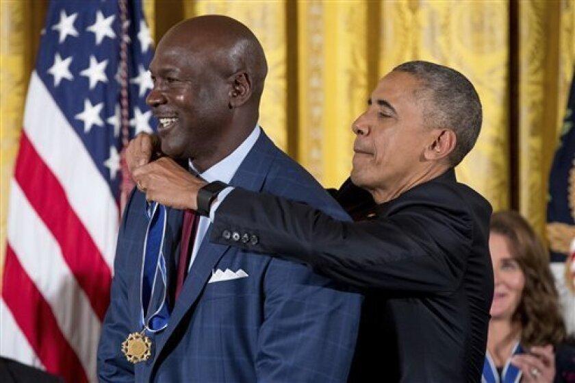 El presidente Barack Obama coloca la Medalla de la Libertad en el cuello del exbasquetbolista Michael Jordan, durante una ceremonia realizada el martes 22 de noviembre de 2016, en la Casa Blanca
