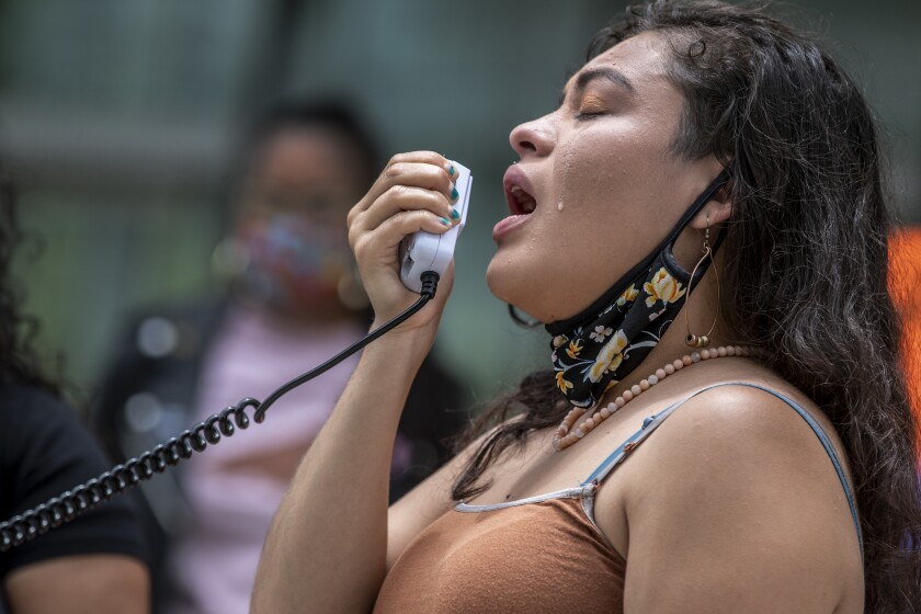 Claudia Rueda cries while speaking into a handheld device