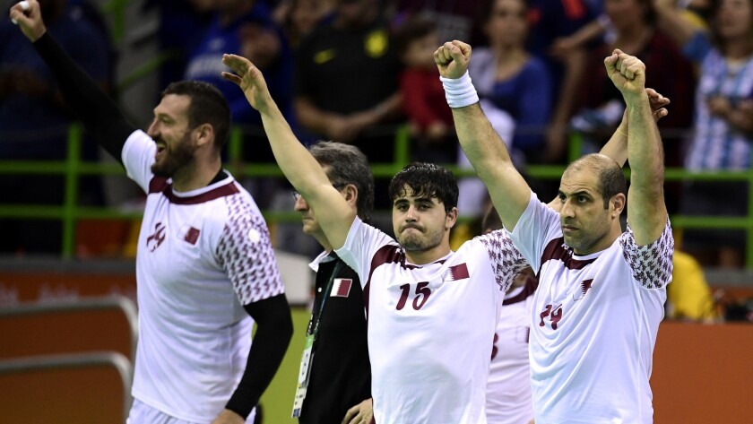 Members of the Qatar handball team celebrate after defeating Argentina in a preliminary-round game Monday.