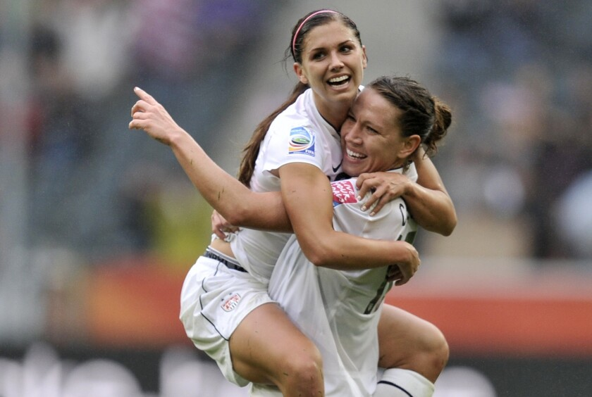 United States' Alex Morgan is carried by United States' Lauren Cheney in celebration after she score