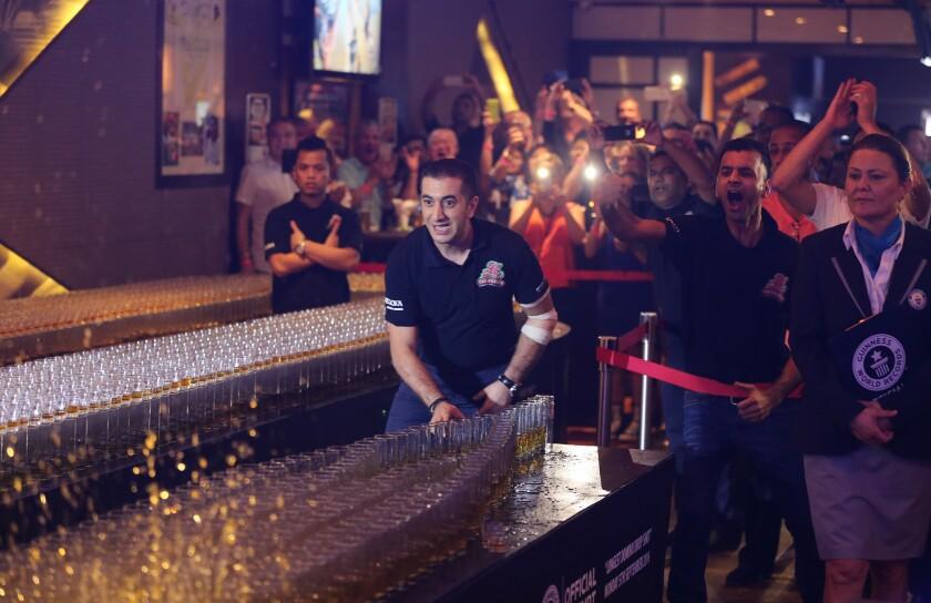 Ahmad Taher, gerente de comidas y bebidas de Citymax Hotels en Dubái, Emiratos Árabes Unidos, tumba un vaso de whisky y desata un efecto dominó durante un evento para lograr el récord mundial de efecto dominó con vasos de whisky, El Huddle Sports Bar & Grille, en Bur Dubai, rompió el récord mundial con 6.000 vasos de bebida energizante y vasos de whisky, bajo la supervisión de una observadora del Libro de Récords Guinness. (AP Foto/Kamran Jebreili)