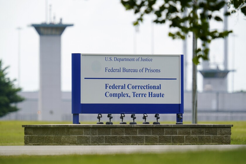 A sign reads U.S. Department of Justice, Federal Bureau of Prisons, Federal Correctional Complex, Terre Haute