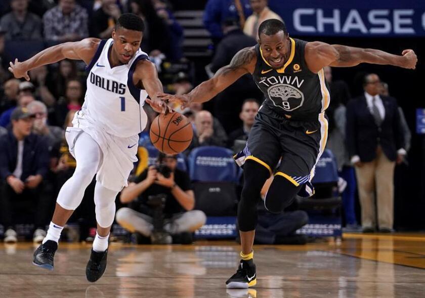 El jugador Dennis Smith Jr. (i) de los Dallas Mavericks en acción ante Andre Iguodala (d) de los Golden State Warriorsdurante el partido de baloncesto de la NBA entre Dallas Mavericks y Golden State Warriors que se disputó, en el Oracle Arena de Oakland, California (EE.UU.). EFE
