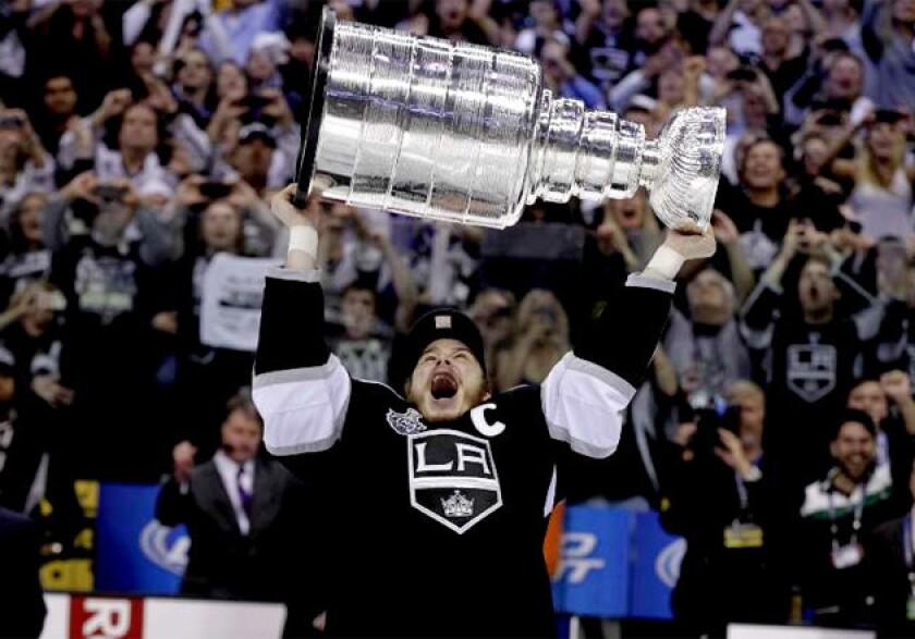 Los Angeles Kings' Dustin Brown hoists the Stanley Cup in June 2012.