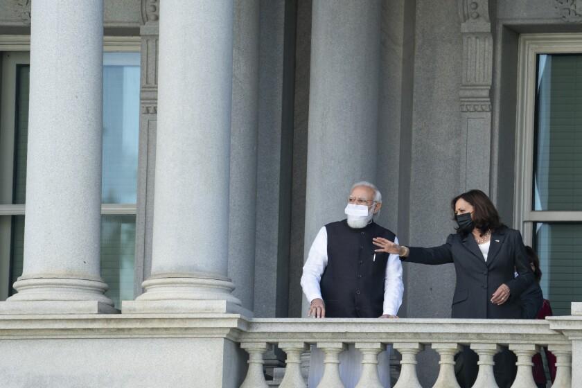 Kamala Harris talks with Narendra Modi on the balcony of the Eisenhower Executive Office Building.
