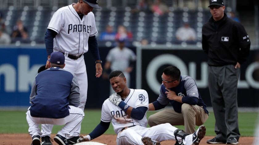 The San Diego Padres' Allen Cordoba reacts after injuring himself sliding to second base during a baseball game against the Texas Rangers on May 9, 2017, in San Diego.