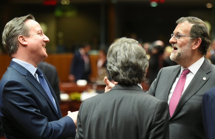 British Prime Minister David Cameron, left, speaks with Spanish Prime Minister Mariano Rajoy, right, during a round table meeting at an EU summit in Brussels on Thursday, Feb. 18, 2016. European Union leaders are holding a summit in Brussels on Thursday and Friday to hammer out a deal designed to k