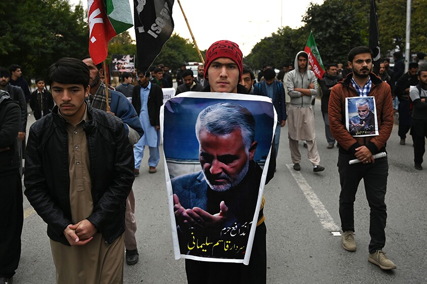 Protesters carry posters with the image of slain Iranian Gen. Qassem Suleimani during a demonstration in Islamabad, Pakistan, on Friday.